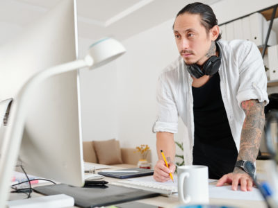 Pensive designer reading e-mail from client when drawing logotype for a big company
