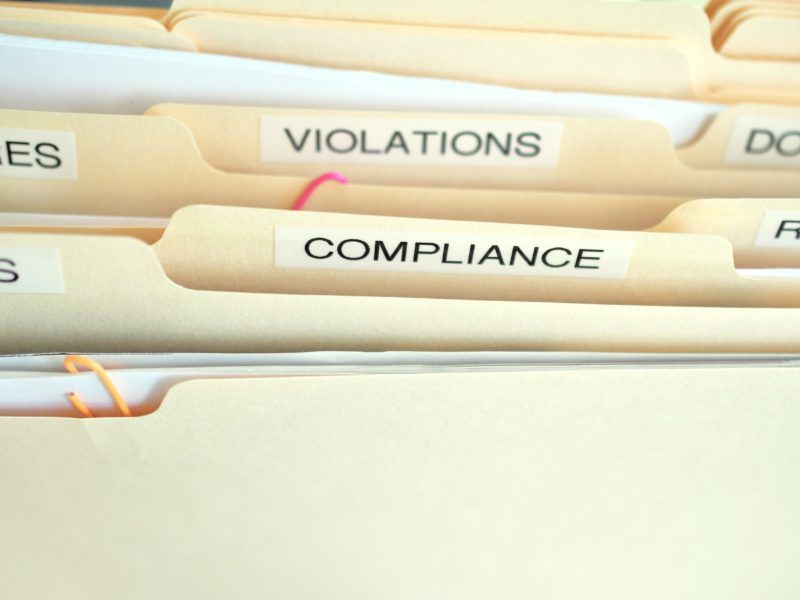 compliance-in-the-workplace-folders-labeled-compli-PG4K38W