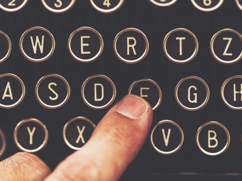Finger on vintage typewriter machine pushing the F key