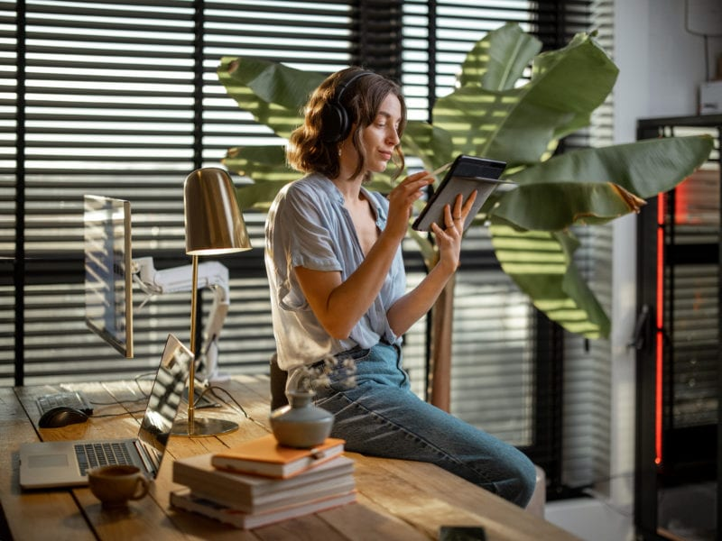 Young woman works on a touchpad, feeling comfortable at cozy home office with a green plant on the background